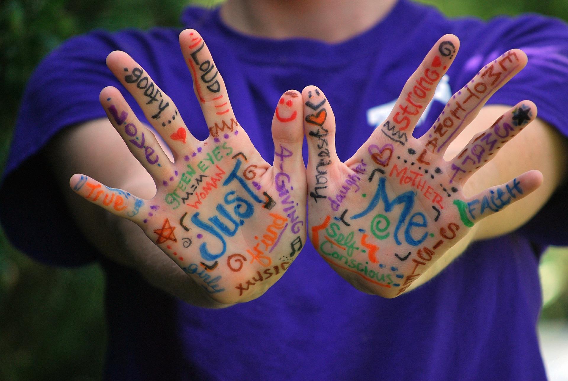la imagen muestra unas manos de un niño con palabras escritas